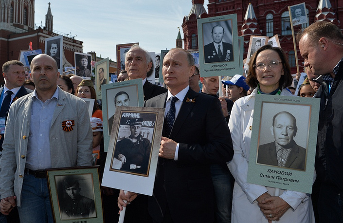 Vladimir Putin holds a portrait of his father at the rally