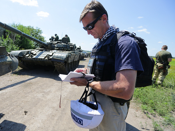 An OSCE observer taking notes as DPR troops withdraw military hardware