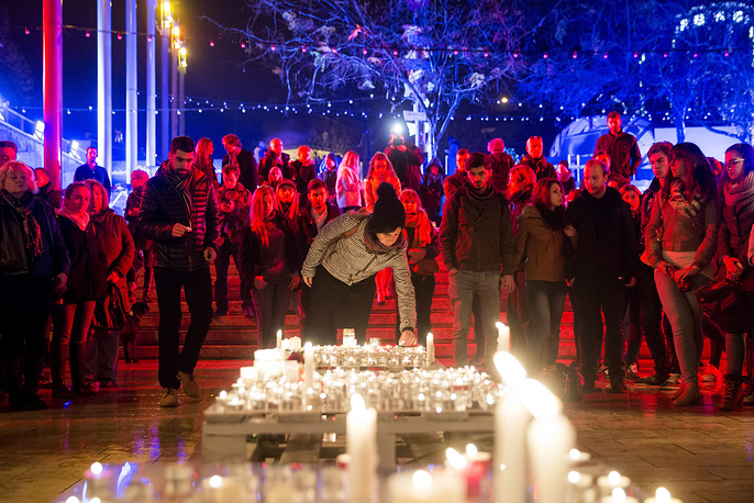 People lighting candles to pay tribute to the victims of the Paris attacks in Budapest, Hungary