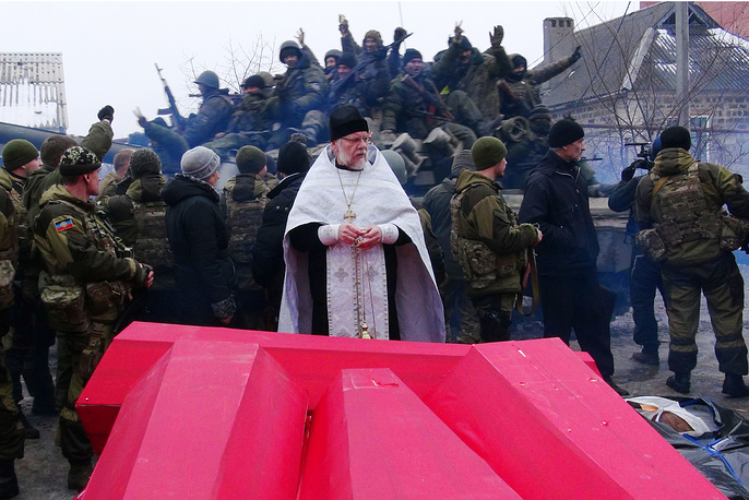 Orthodox priest reading the last rites during a ceremony at Donetsk Airport where the bodies of Ukrainian government servicemen were handed over to Kiev's representatives, January 22, 2015