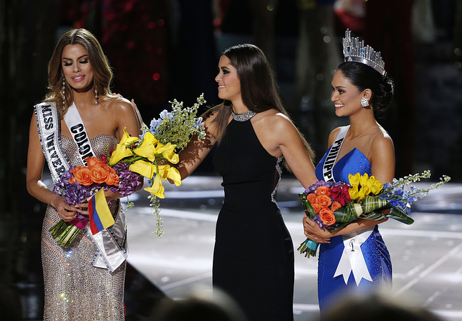 Former Miss Universe Paulina Vega taking away the flowers and sash from Miss Colombia Ariadna Gutierrez before giving them to Miss Philippines Pia Alonzo Wurtzbach