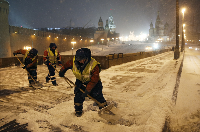 Municipal workers cleaning a bridge through the Moskva River during heavy snowfall near the Kremlin in Moscow