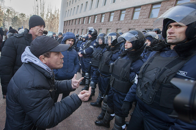 A man faces police officers during a protest in front of the parliament building in Chisinau, Moldova, 21 January 2016. The supporters of politics platform 'Demnitate si Adevar' (lit. Dignity and Truth), socialists and the 'Our Party' party, attended a protest against the new government, asking for early parliamentary elections.