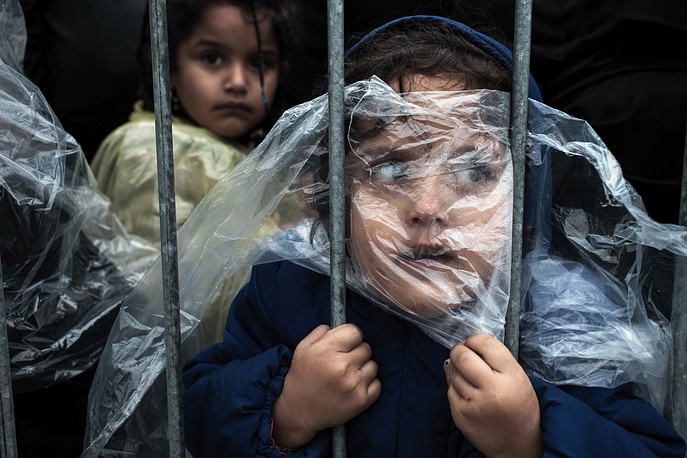 Slovenian photographer Matic Zorman, 1st prize singles in the People category. The picture shows a child covered with a raincoat while she waits in line to register at a refugee