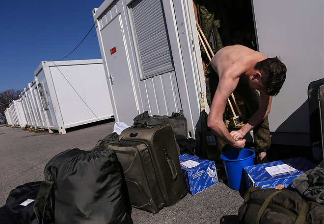 Russian soldier with his luggage outside a prefabricated house at Hmeimim airbase