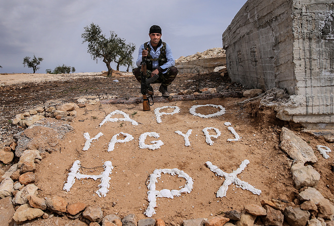 An armed Kurdish fighter near the Syrian-Turkish border. The message reads: APO (in reference to Abdullah Ocalan), YPG YPJ (acronyms for the People's Protection Units and the Women's Protection Units), HPX (acronym for Kurdish self defense)