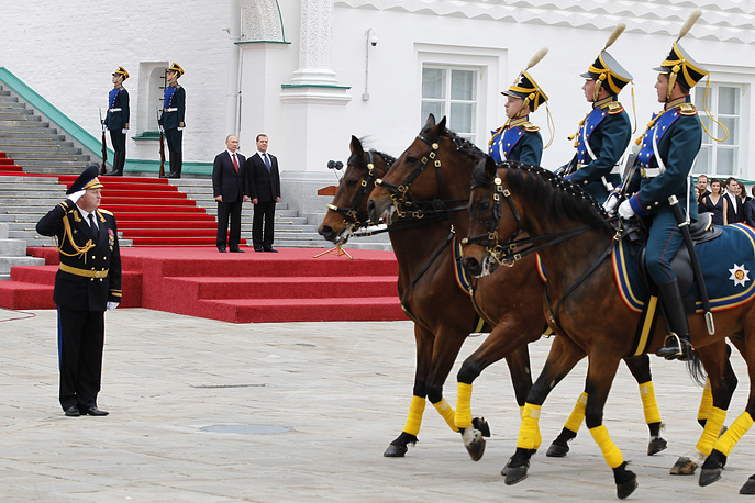 Dmitry Medvedev and Vladimir Putin watching mounted honour guards during a parade of the Kremlin Regiment in Cathedral Square