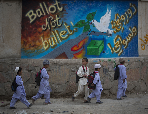 "School children pass by a graffiti reading, ""ballot not bullet"" on their way on the outskirts of Kandahar, southern Afghanistan"