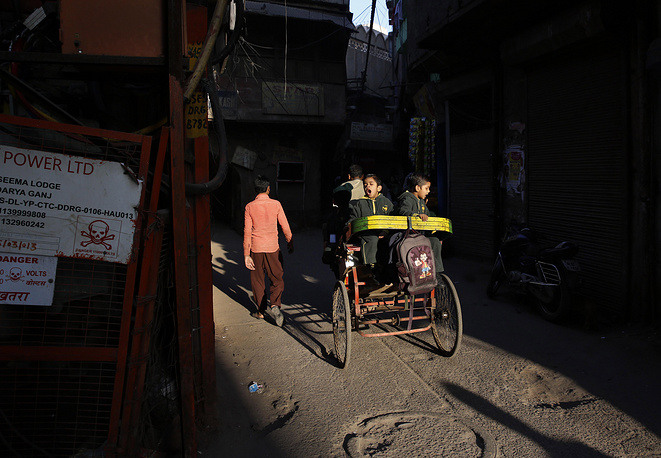 Indian children make their way to school at sunrise as they sit on the back of a cycle rickshaw in New Delhi, India