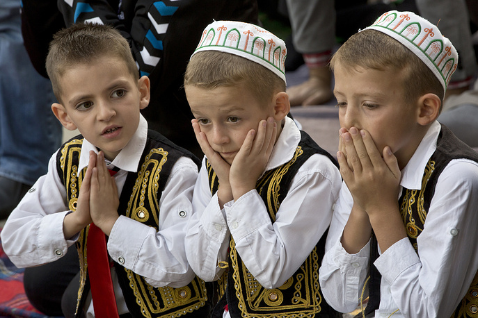 Kosovar children pray outside Sultan Mehmet Fatih mosque in Pristina