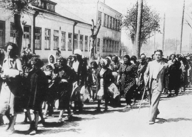 Jewish women convoyed by a Lithuanian self-defense fighter collaborating with the Nazis, 1941