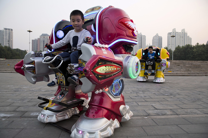 Children ride mechanical robots at a park in Beijing, China, Sept. 30