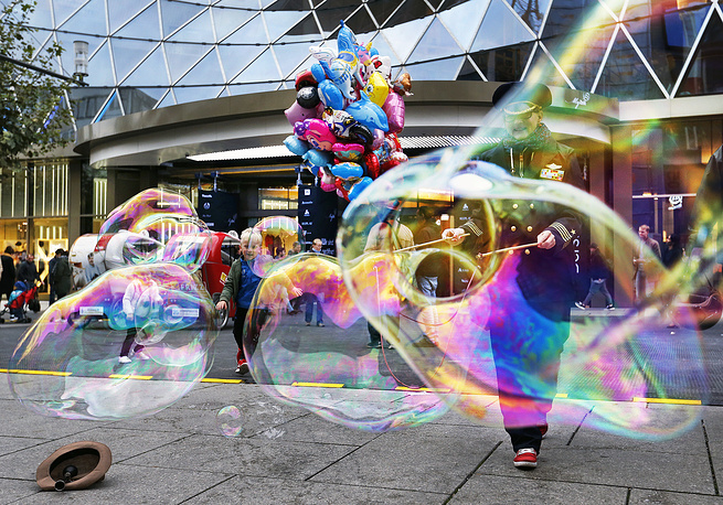 A woman makes bubbles in the main shopping street in Frankfurt, Germany, Ocober 11
