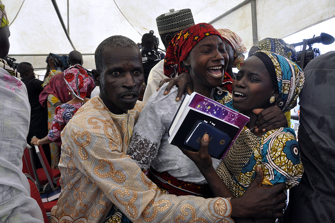 One of the kidnapped Chibok schoolgirls celebrates reunion with family members in Abuja, Nigeria, October 16
