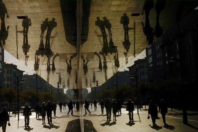 Silhouettes of a walkers reflected in the mirrors of a building in Pamplona, Spain, October 26