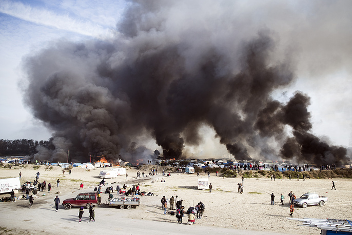 "Smoke billows from a fire after tents and shacks were set ablaze in the makeshift migrant camp known as ""the jungle"" near Calais, France, October 26"