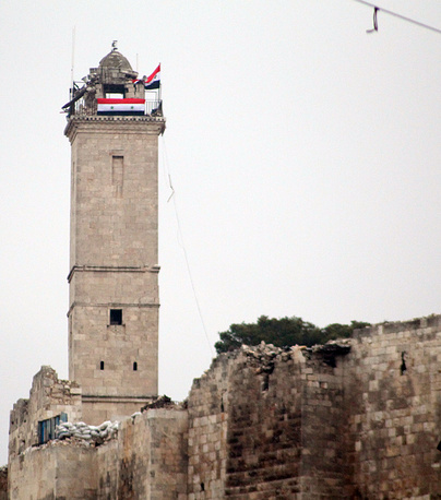 Syrian flags placed on one of Aleppo Citadel Towers, in the eastern neighborhoods of Aleppo
