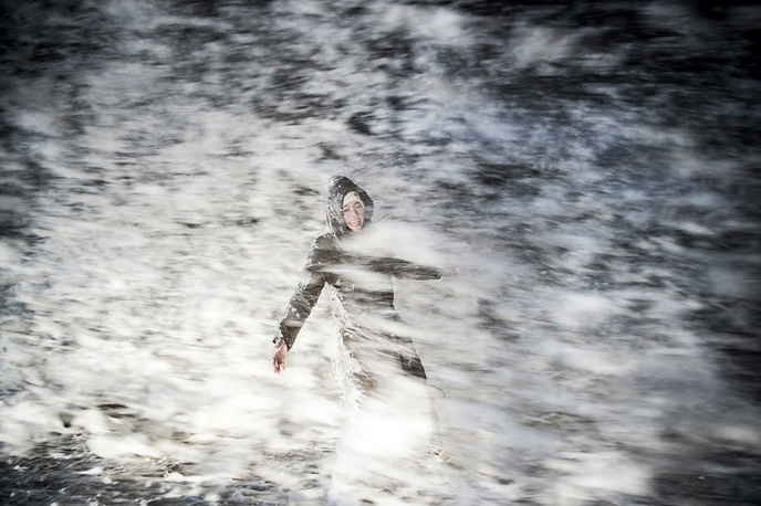 The sea sprays a woman as she walks on the coast, in Hirtshals, the northern part of Jutland, Denmark, December 26