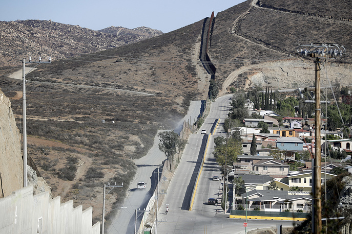 A Border Patrol vehicle driving by the border fence in Tecate, California, along the metal barrier, seen from Tecate, Mexico