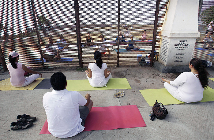 """People practicing yoga on both sides of the US-Mexico border fence as they take part in the """"Yoga without borders"""" encounter in Tijuana, Mexico, 2008"""