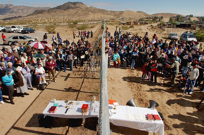 For almost two decades Mexico-US border in the Mexican town of Anapra had been the place where the Mass on Day of the Dead was celebrated to remember migrants died trying to cross the fence. Photo: A mass at the Mexico-US border during Day of the Dead celebrations in Anapra, Mexico, 2004
