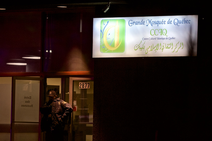 A Quebec police officer stands guard after a shooting at the Quebec Islamic Cultural Centre in Quebec City, Canada