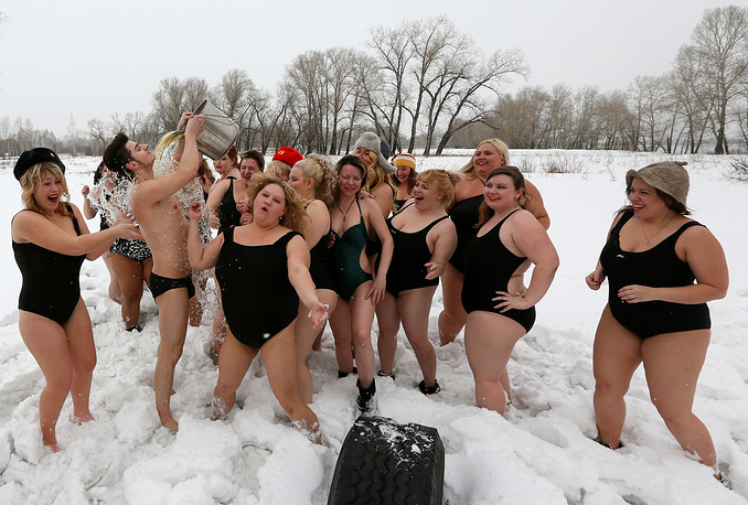 Models of the SibPlus Models agency and participants of the Miss Doughnut beauty competition watch their trainer pouring a bucket of cold water over himself at the Polar Bear winter swimmers club in Krasnoyarsk, Russia, March 4