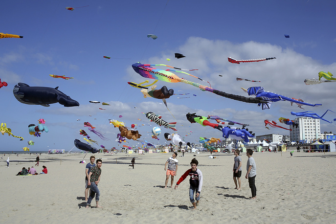 Boys play soccer as kites are seen in the sky during the 31st International Kite Festival in Berck, France, April 6