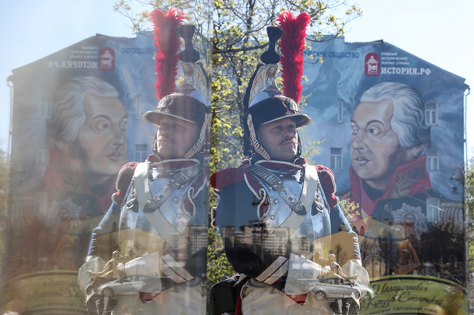 People in costumes by a wall mural on the side wall of a house at Volkhonka Street, central Moscow, showing Field Marshal of the Russian Empire Mikhail Kutuzov who led the Russian Army against Napoleon during the French invasion of Russia in 1812, May 3