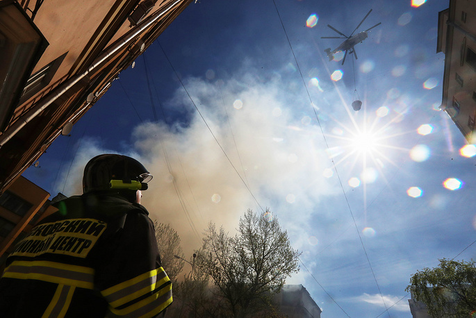 A helicopter drops water while battling a fire at a building in central Moscow, Russia, May 5