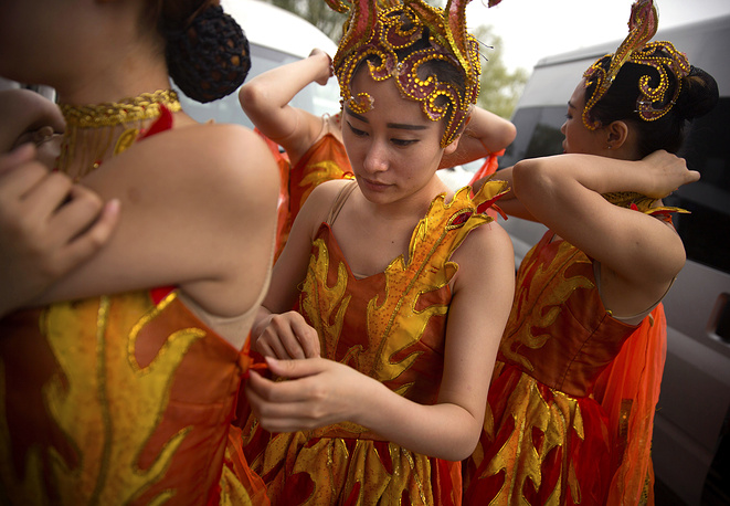 Performers adjust their costumes backstage before the opening ceremony of the Dragon Boat festival at the Olympic Water Park in Beijing, May 30