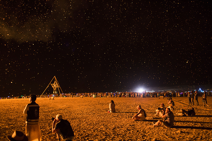 Festivalgoers look on an art installation as it is burning during the Israel Midburn Festival in the Negev desert southern Israel, May 31
