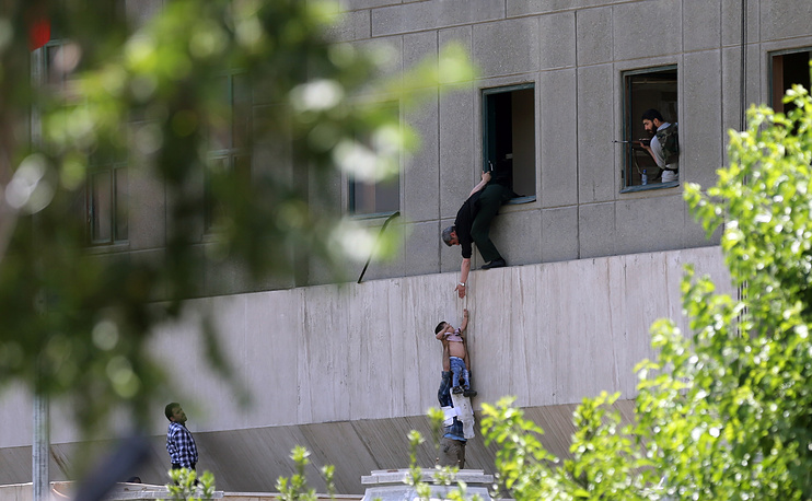 Iranian policemen try to help some civilians fleeing from the parliament building during an attack in Tehran