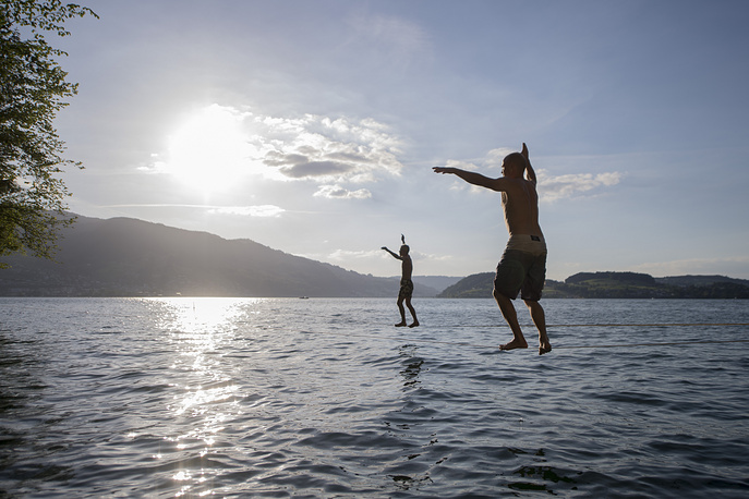 Two men walk for fun on ropes over Lake Lucerne in Kehrsiten, Switzerland, June 17