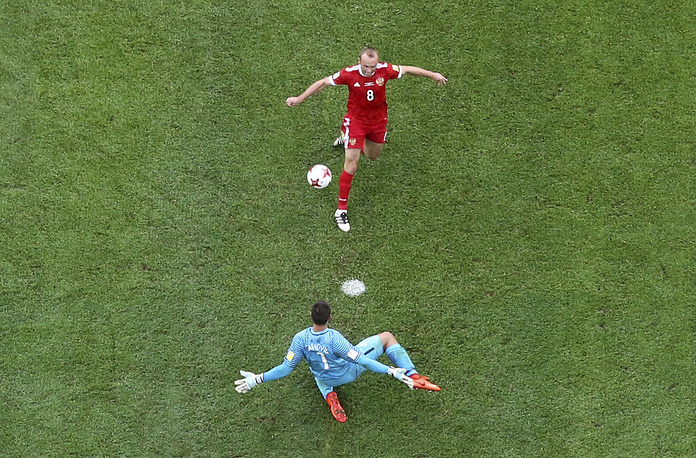 Russia's Denis Glushakov chips the ball over New Zealand goalkeeper Stefan Marinovic to score the opening goal during the Confederations, Cup Group A soccer match between Russia and New Zealand, at the St.Petersburg stadium in St.Petersburg, Russia, June 17