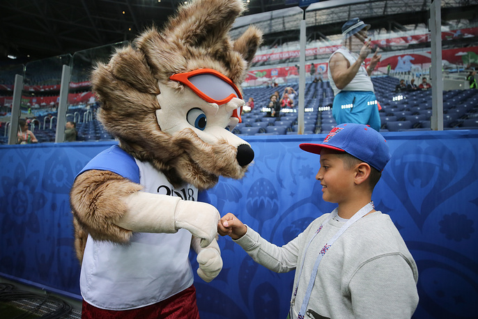 Zabivaka the Wolf, the 2018 FIFA World Cup official mascot, greets a young fan ahead of a match between New Zealand and Portugal at Saint Petersburg Stadium