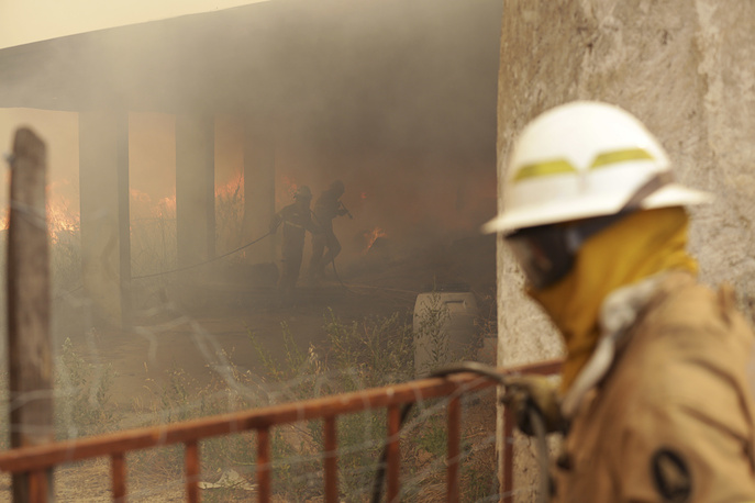 Firefighters of the National Republican Guard battle flames approaching houses in the village of Sao Jose das Matas, near Macao, Portugal