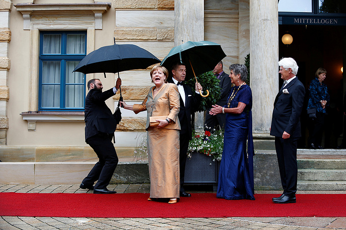 German Chancellor Angela Merkel reacts as she arrives at the red carpet for the opening of the Bayreuth Wagner opera festival outside the Gruener Huegel (Green Hill) opera house in Bayreuth, Germany July 25