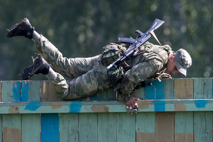 Russian serviceman climbing a wooden fence during the Scout Trail obstacle course