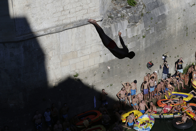 Spectators watch as a diver jumps from the Old Mostar Bridge during 451th traditional annual high diving competition, in Mostar, Sarajevo, July 30