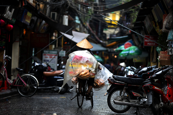 A street vendor selling bread rides a bicycle on a street in Hanoi, Vietnam,  August 17