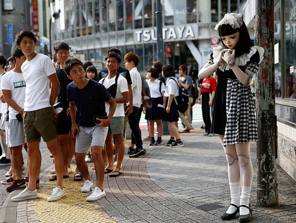 "Pedestrians look at ""doll"" model Lulu Hashimoto standing on the street in Tokyo, Japan, August 23"