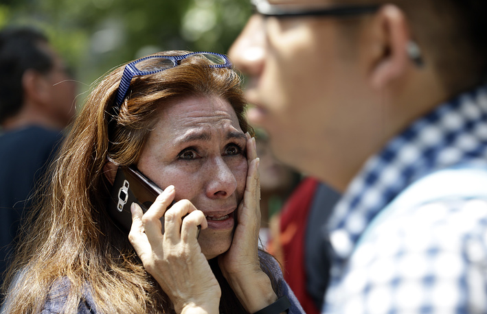 A woman tries to reach people on her cellphone after she evacuated with others to Paseo de la Reforma Avenue after an earthquake in Mexico City
