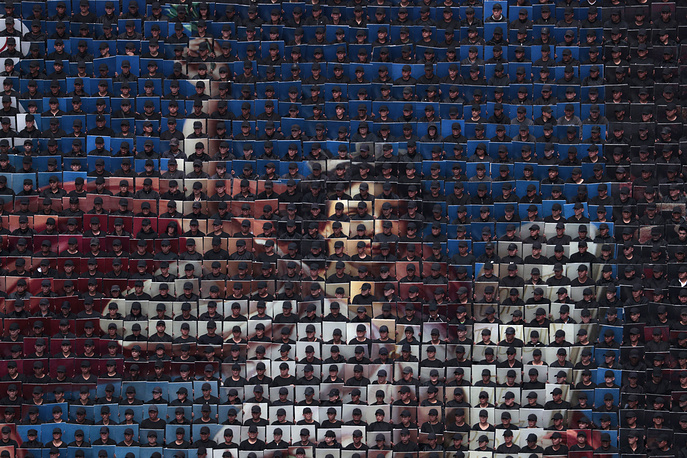 Hundreds of military troops hold placards to create a mosaic of Petronilo Monroy's allegorical figure The Constitution, during the annual Independence Day military parade in Mexico City, September 16