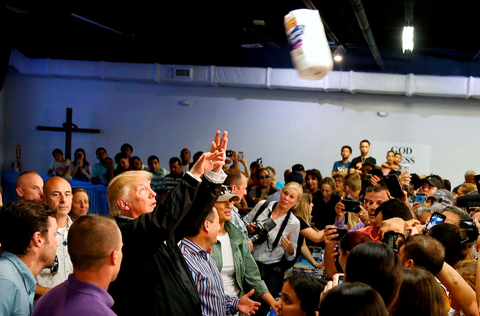 US President Donald Trump throws rolls of paper towels into a crowd of local residents affected by Hurricane Maria as he visits Calgary Chapel in San Juan, Puerto Rico, US, October 3