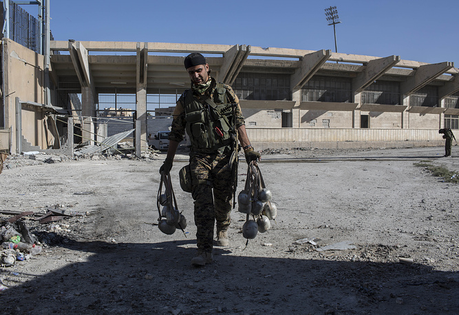 A member of Syrian Democratic Forces carries explosives at the stadium in Raqqa