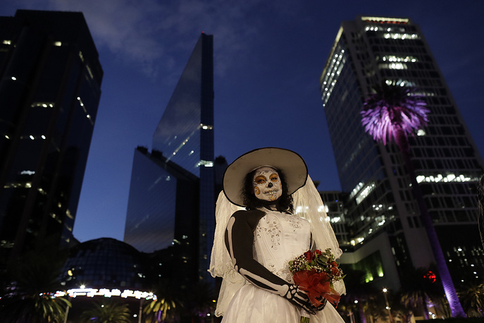 """A woman, dressed as a skeleton bride, poses for pictures during the Grand Procession of the """"Catrinas"""" in Mexico City"""