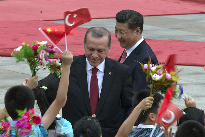 Turkey's President Recep Tayyip Erdogan and Chinese President Xi Jinping are greeted by Chinese children jumping and waving Turkish and Chinese national flags during a welcome ceremony at the Great Hall of the People in Beijing, 2015