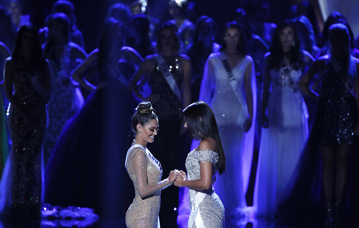 Miss South Africa Demi-Leigh Nel-Peters and Miss Colombia Laura Gonzalez hold hands before they announce the winner at the Miss Universe pageant in Las Vegas