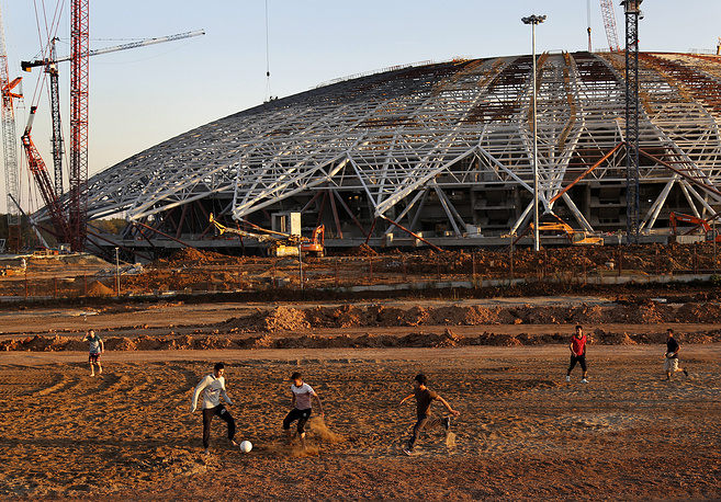 Construction workers play football just outside the construction site of the World Cup stadium in Samara
